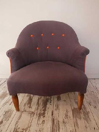 Fauteuil crapaud à passepoil et boutons orange. Le Crapaud est un des fauteuils les plus confortables. Il est parfait pour habiller un intérieur moderne.